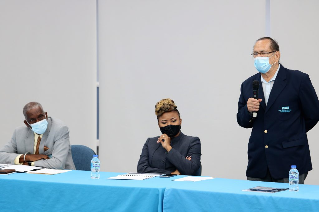 MIC-IT Chairman, Professor Clément Imbert (standing) welcomes Minister of Education, Dr. the Honourable Nyan Gadsby-Dolly. Seated is MIC-IT Deputy Chairman, Mr. Keith Toby.